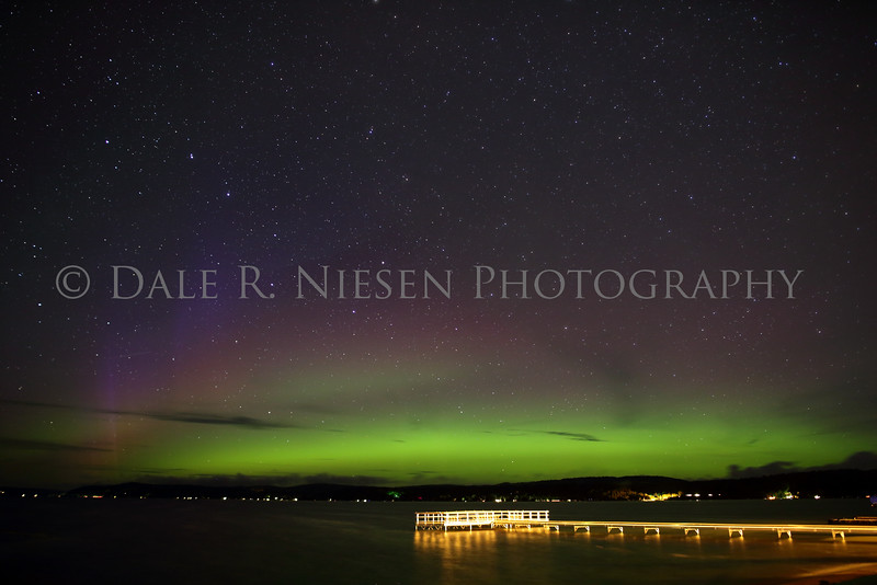 The northern lights and starts above Crystal Lake from the public park in Beulah, Michigan.